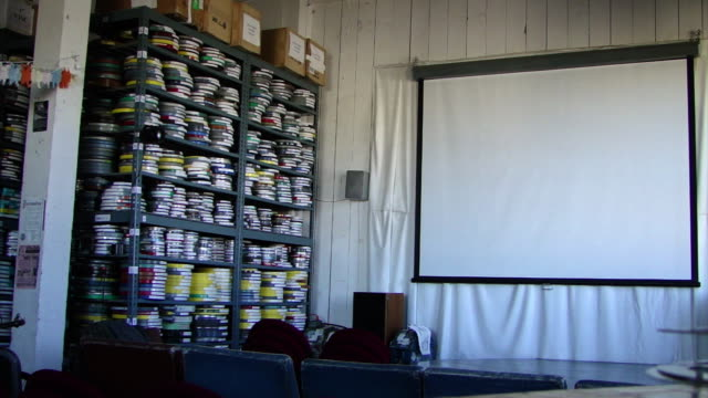view of projector screen hanging on the wall with a shelf full of film canisters on the left side and chairs in the foreground, in a film archive in... - film reel stock videos & royalty-free footage