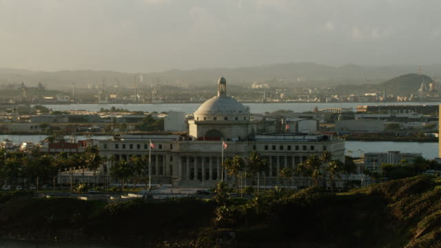 WS AERIAL POV View of Puerto Rico capitol building with flags waving in foreground / Old San Juan, San Juan, Puerto Rico, United States