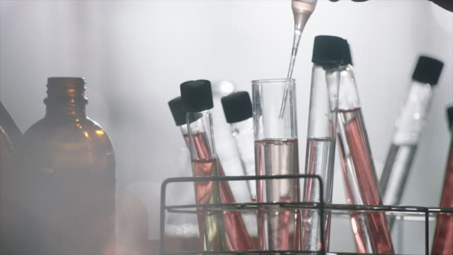 View of putting the red solution from a spuit into a glass tube