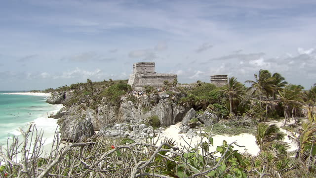 WS View of Pyramid El Castillo (The Castle), Tourists visible around pyramid, on beach and in water / Tulum, Quintana Roo, Mexico