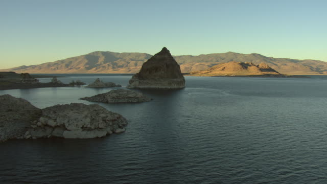 vidéos et rushes de ws aerial view of pyramid tufa in shadow in pyramid lake in morning / nevada, united states - roche sédimentaire