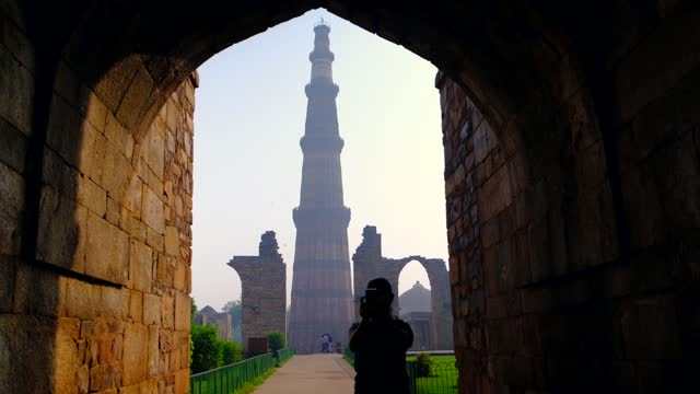 view of qutab minar framed under a stone archway, flanked on sides by ruins where tourists in silhouette take photo video selfie on their smart mobile phone device during the pandemic in 2020 - minareto video stock e b–roll