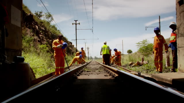 WS POV View of rail road workers standing outside of train tunnel / South Africa