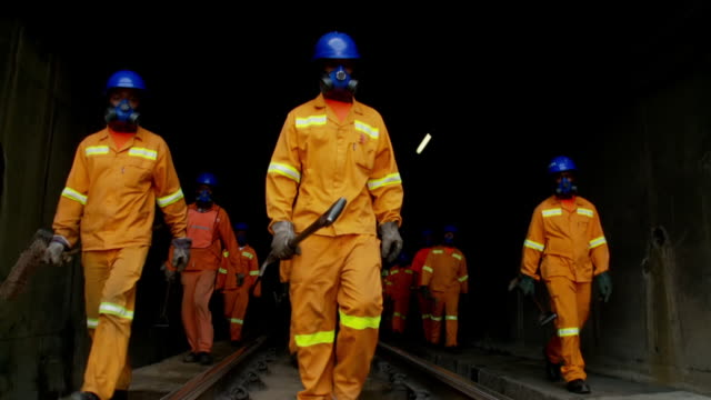 ws view of rail road workers walking out of train tunnel / south africa - オーバーオール点の映像素材/bロール
