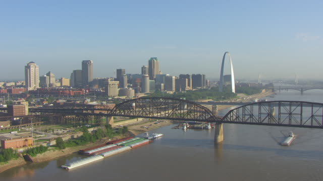 ws aerial view of railroad bridge and highway 40 bridge and mississippi river in foreground to downtown with gateway arch / st louis, missouri, united states - 西方拡大点の映像素材/bロール
