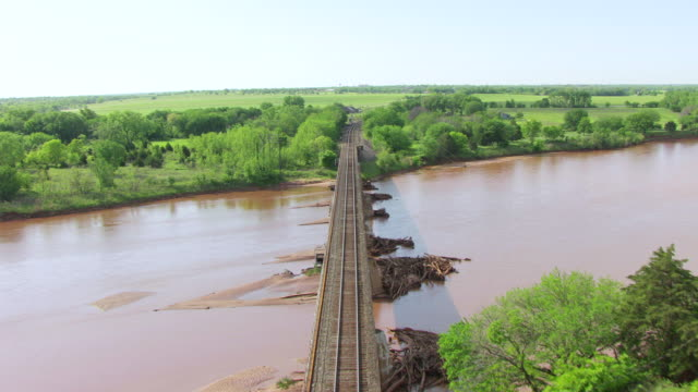 vídeos de stock, filmes e b-roll de ws aerial view of railroad tracks over river with surrounding forest  / guthrie, oklahoma, united states - perspectiva espacial