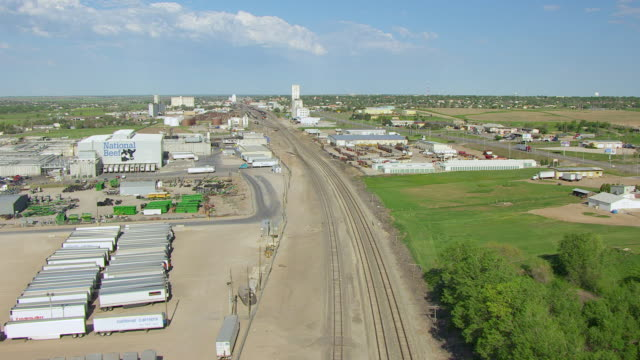 ws aerial view of railroad tracks through city with car moving on bridge / dodge city, kansas, united states - kansas stock-videos und b-roll-filmmaterial