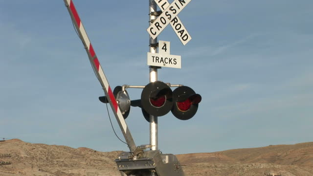 view of railway level crossing gate opening up in wyoming united states - level crossing stock videos & royalty-free footage