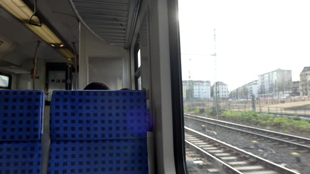 view of railway through train's window which start depart from platform train station. window side view  during commute and travel by train. - bahnhof stock-videos und b-roll-filmmaterial