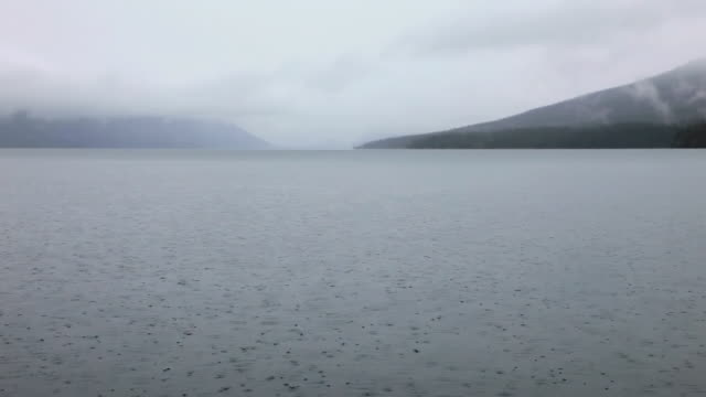 ws view of rainy misty day with low clouds on mountain lake / west glacier, montana, united states - 池点の映像素材/bロール