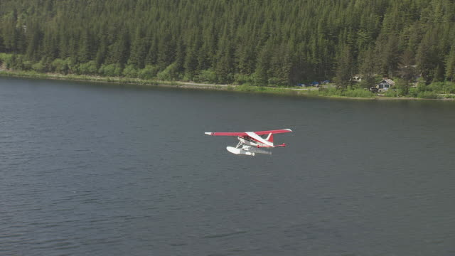 WS AERIAL ZI View of red and white Beaver Floatplane flying over water / Cordova, Alaska, United States
