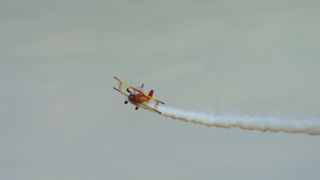 ws ts view of red and yellow airplane flying in the sky emitting smoke / united states - 曲芸点の映像素材/bロール