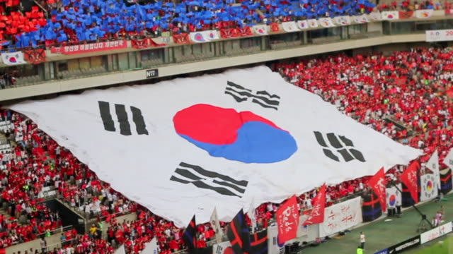 ws slo mo view of red devil (korean cheering squad) hand raised huge south korean flag to fold at the seoul world cup stadium in sangam / seoul, south korea  - south korea stock videos & royalty-free footage