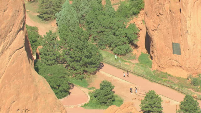 ms ds aerial view of red rock formation and visitors walking on pathway between rock formations / colorado springs, colorado, united states - 砂岩点の映像素材/bロール