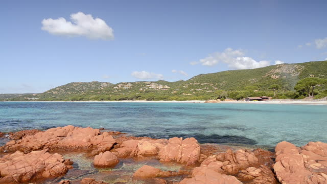 WS View of Red rocks and sandy beach with blue water, nature preserve / Palombaggia, Corsica, France