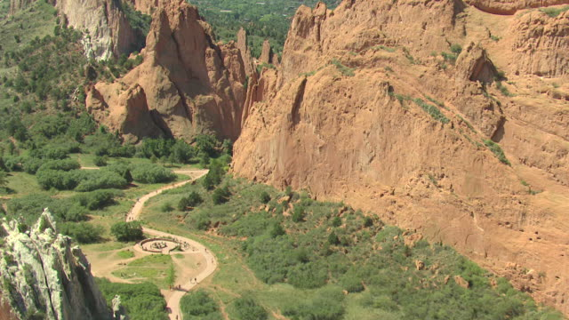 MS AERIAL View of red rocks formations with people walking on trails at base during daytime sunlight / Colorado Springs, Colorado, United States
