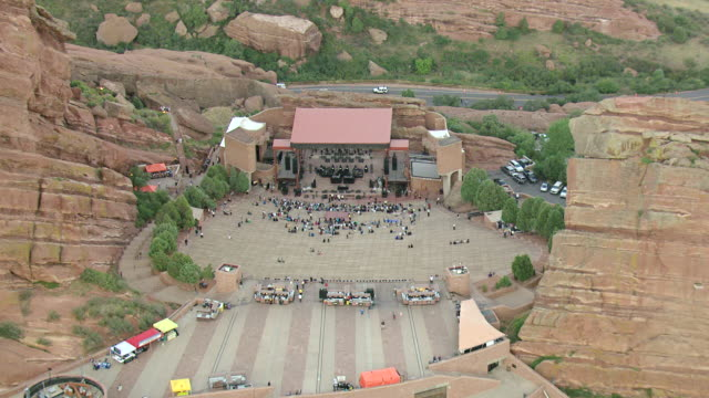 MS TD AERIAL View of red rocks mountain park of people congregating on amphitheater steps in front of stage / Denver, Colorado, United States