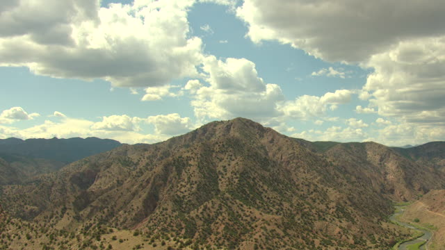 ws ds aerial view of red rocky mountains under sun filled sky with clouds and arkansas river in valley in pueblo county / colorado, united states - pueblo colorado stock videos & royalty-free footage