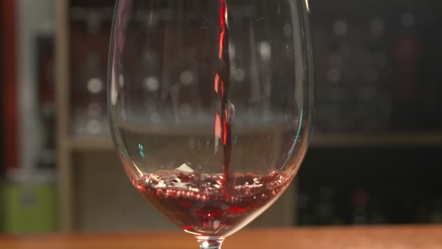 view of red wine being poured into a wine glass - wine glass stock videos & royalty-free footage