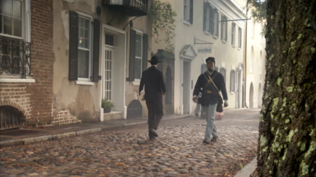 ws pan view of reenactment people walking down cobblestone street / charleston, south carolina, united states - 1865 stock videos & royalty-free footage