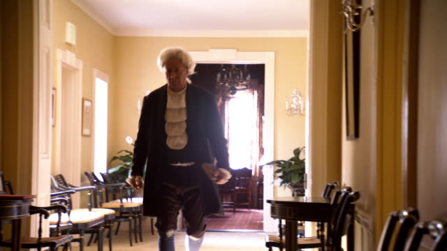 ws r/f pan view of reenactment president james madison walks through house / baltimore, maryland, united states  - ジェームズ・マディソン点の映像素材/bロール