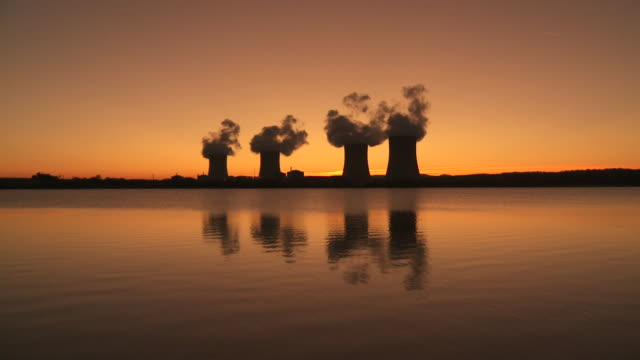 vidéos et rushes de ws view of reflection in water of nuclear plant at sunset / cattenom, lorraine, france - centrale nucléaire