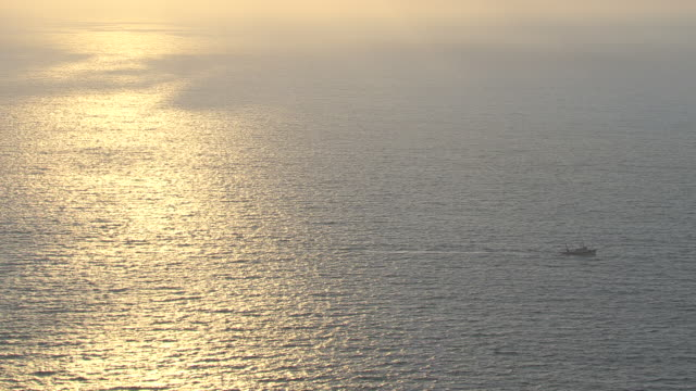 ws aerial view of reflection of sun water and fisher boat floating / lefkada,corfu, ionian islands, greece - greece stock videos & royalty-free footage