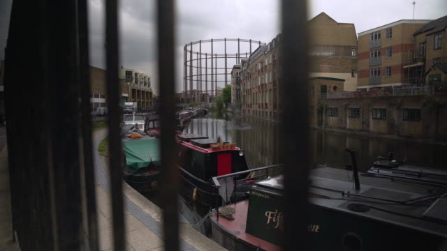 vidéos et rushes de view of regent's canal through metal fence, london - hackney