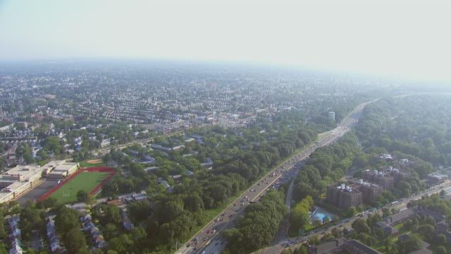 stockvideo's en b-roll-footage met ws aerial view of residential area along highway in city / new york, united states - tweebaansweg