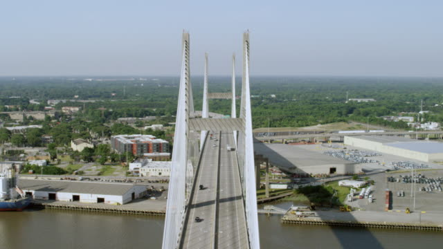 WS AERIAL POV View of residential district with suspension bridge in front / Savannah, Georgia, United States