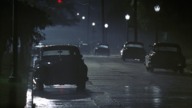 ws view of residential street traffic with rain - stationary stock videos & royalty-free footage
