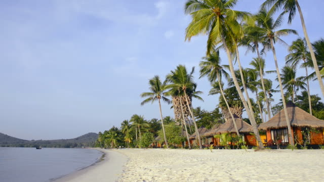 WS View of Resort with seaside bungalows and palm trees at sandy beach, hat chao mai marine national park / Ko Mook, Trang, Thailand