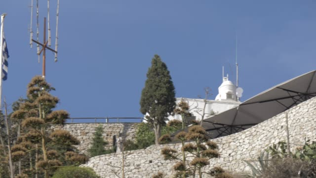 view of restaurant and church at the summit of mount lycabettus from below, athens, greece, europe - lycabettus hill stock videos & royalty-free footage