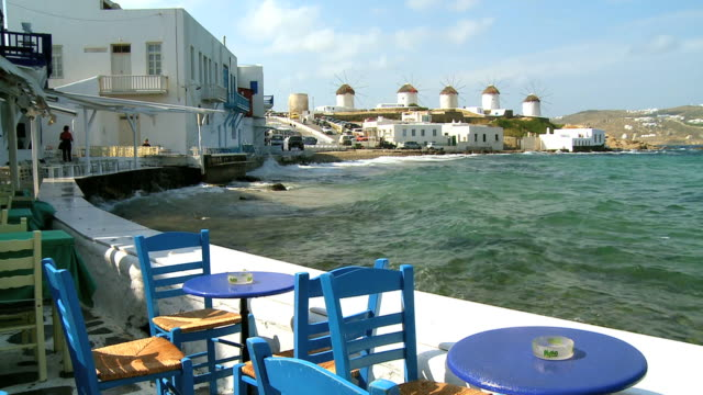 ws view of restaurant and ocean with windmills on hill / mykonos, cyclades, greece - mykonos stock videos & royalty-free footage