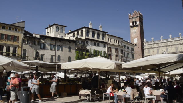 MS View of Restaurant at Piazza delle Erbe, palace facade and market stalls / Verona, Veneto, Italy