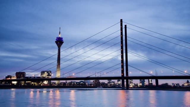 ws t/l view of rheinturm (tv tower), rheinkniebrã¼cke and rhine river at dusk / dã¼sseldorf, north rhine-westphalia, germany - デュッセルドルフ点の映像素材/bロール