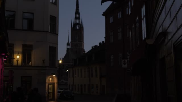 view of riddarholmen church at dusk from gamla stan, stockholm, sweden, scandinavia, europe - circa 13th century stock videos and b-roll footage