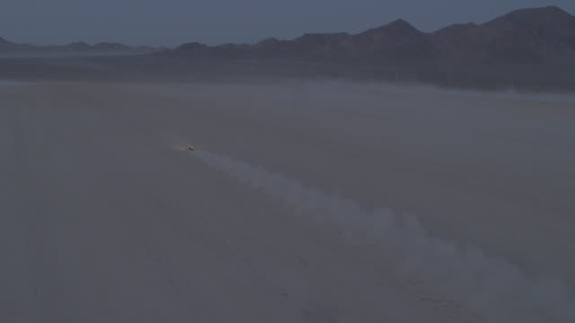 """ws aerial ts pan view of riding car in desert / new york city, united states"" - dirt track stock videos & royalty-free footage"