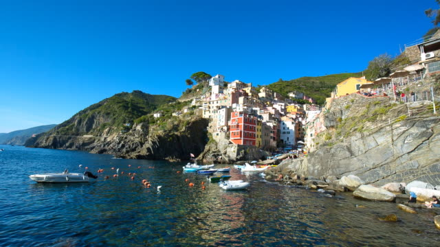 View of Riomaggiore Village in Cinque Terre and surrounding seascape with anchored tourboats