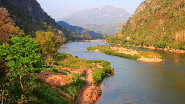 ws view of river bank with people walking by and mountains / nong khio, luang prabang, laos - laos stock videos and b-roll footage