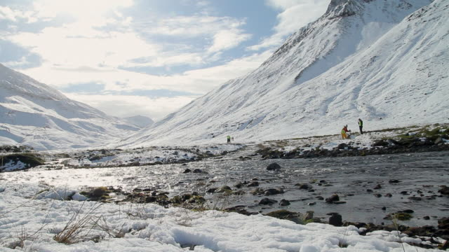 stockvideo's en b-roll-footage met ws view of river flowing and men stand below large sno covered mountain / skagafjorour, nordhurland vestra, iceland  - wiese
