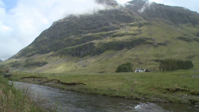 ws view of river flowing near mountain / glencoe, highlands, scotland - scottish highlands stock videos and b-roll footage