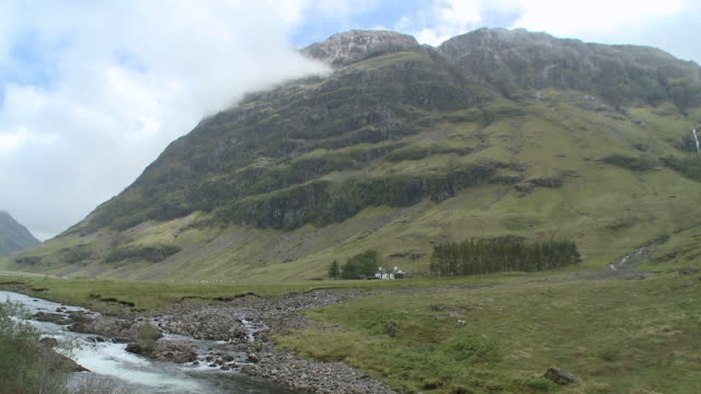 stockvideo's en b-roll-footage met ws view of river flowing near mountain with clouds moving / glencoe, highlands, scotland - schotse hooglanden