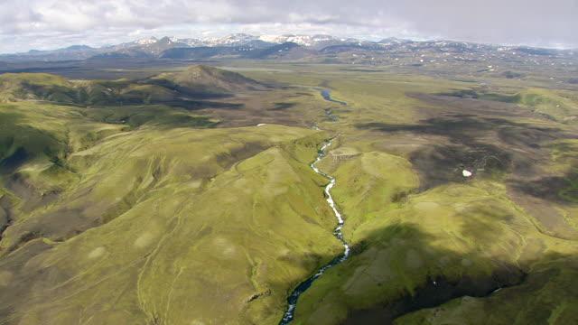 vídeos de stock, filmes e b-roll de ws aerial zi view of river flowing through mountain valley at landmannalaugur / iceland - islândia central