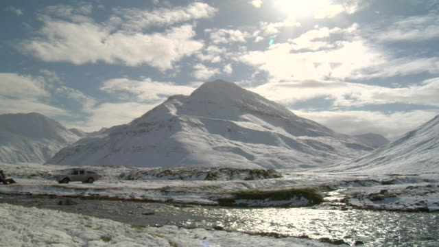 stockvideo's en b-roll-footage met ws view of river flowing with large snow covered mountain peak / skagafjorour, nordhurland vestra, iceland  - wiese