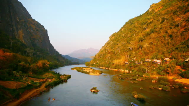 WS View of river in between two mountains with striking orange sunset light and boat moving / Nong Khio, Luang Prabang, Laos