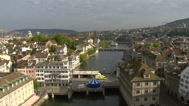 WS AERIAL View of river Limmat and old town with city hall, Fraumunster abbey and Grossmunster church with Zurich Main railway Station / Zurich city, Zurich, Switzerland