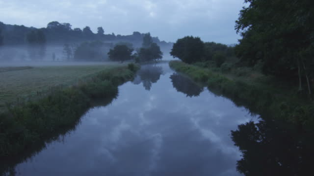 ws view of river with trees during fog in background / godalming, surrey, uk - rosso stock videos & royalty-free footage