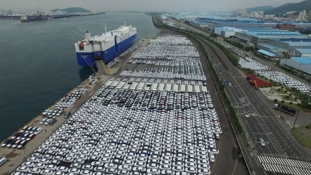 view of road and large group of cars parking in a row at export pier - cars parked in a row stock videos & royalty-free footage
