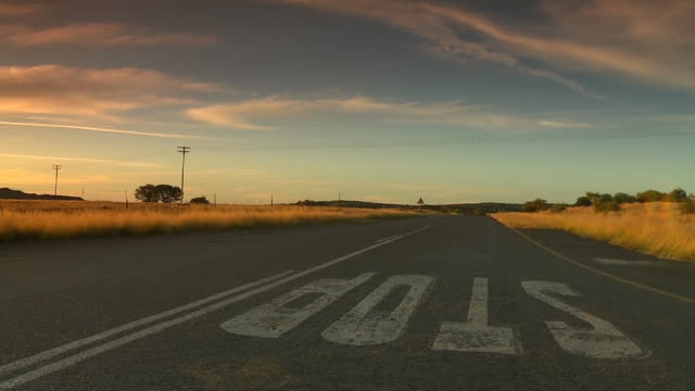 ws la view of road (stop street) at sunset / free state, south africa - telegraph pole stock videos and b-roll footage